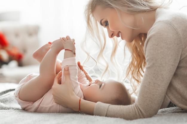 Joven madre con su pequeño bebé en el interior. mamá besa a su hija de 6 meses en casa. pequeños pies de bebé.
