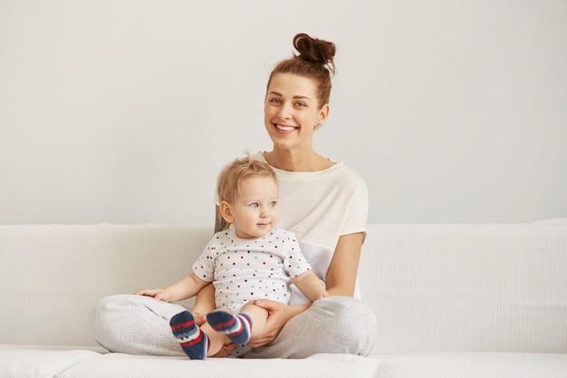 Joven madre con su pequeño hijo de un año vestido con pijama es relajante