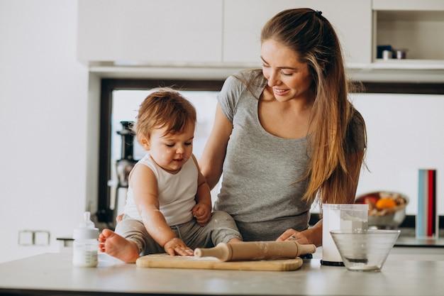 Joven madre con su pequeño hijo cocinando en la cocina