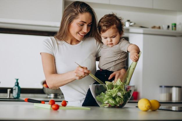 Joven madre con su pequeño hijo haciendo ensalada en la cocina