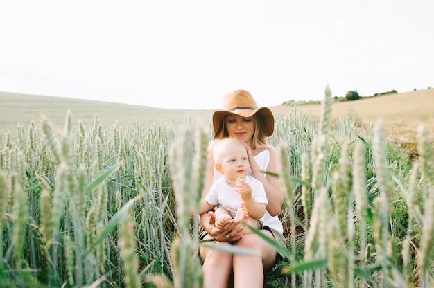 Una joven madre y su pequeño hijo sentado cerca del trigo sobre un fondo verde