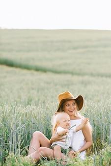 Una joven madre y su pequeño hijo sentados cerca del trigo sobre un fondo verde