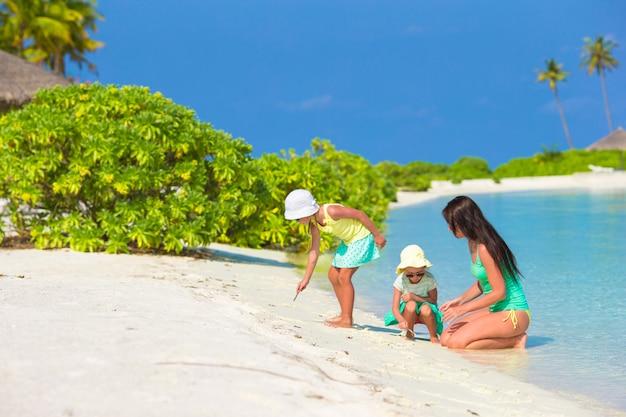 Joven madre y sus dos hijas en la playa exótica en un día soleado