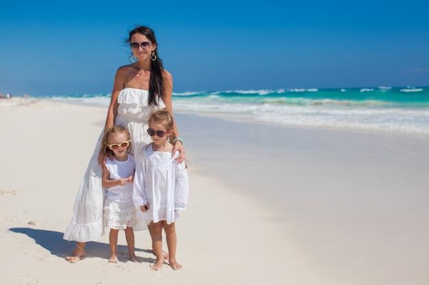 Joven madre y sus dos hijos de moda en la playa exótica en un día soleado