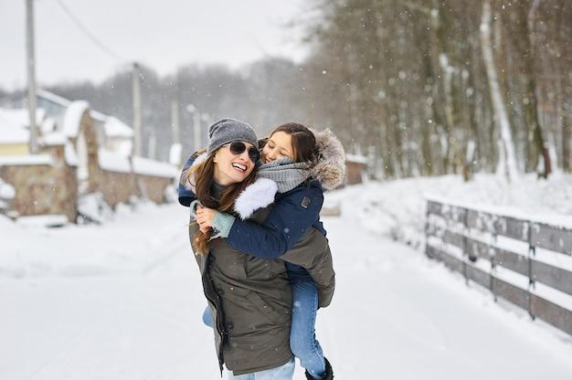 Una joven madre con sus hijos se divierte y juega al aire libre cerca de la casa. vacaciones familiares y concepto de tiempo feliz