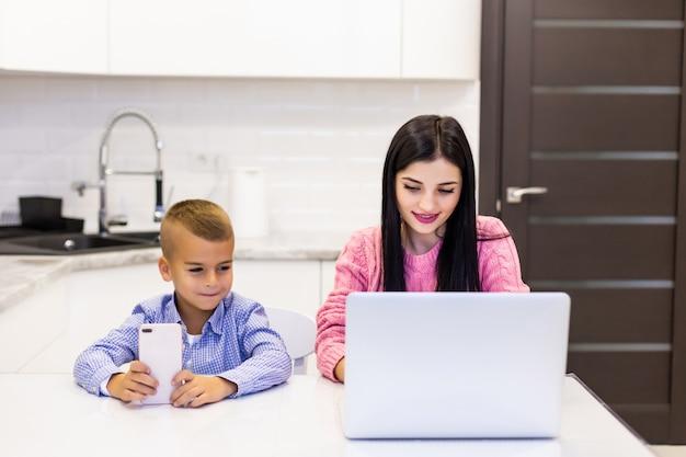 Joven madre trabajando en la computadora portátil en casa, mientras que su hijo está aburrido de jugar en el teléfono