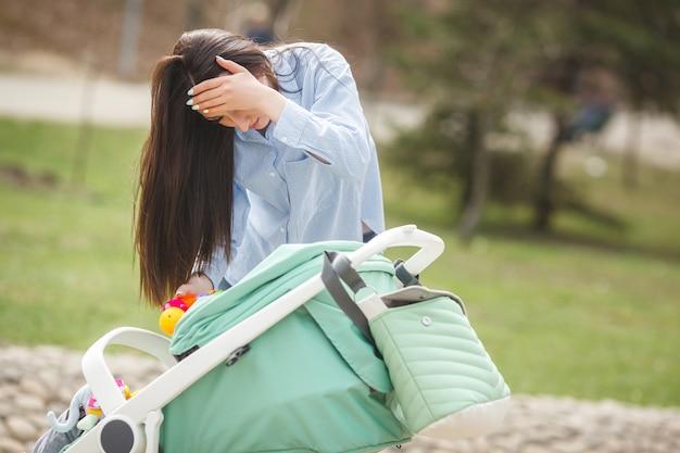 Joven madre tratando de calmar a su pequeño bebé al aire libre