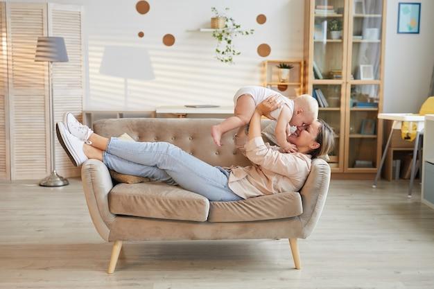 Joven madre vistiendo ropa casual relajante en el sofá levantando a su pequeño hijo, tiro de vista lateral