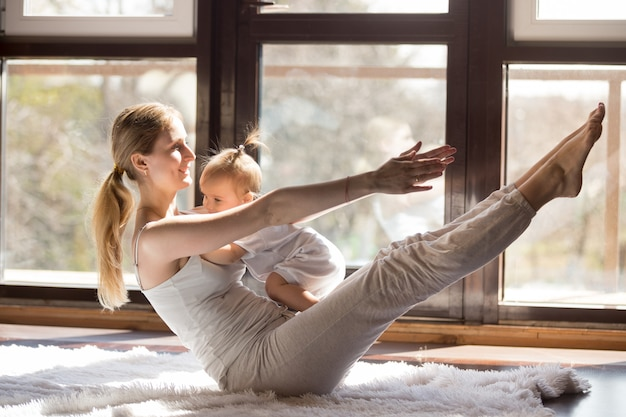 Joven madre yogui en pose de barco con su pequeña hija