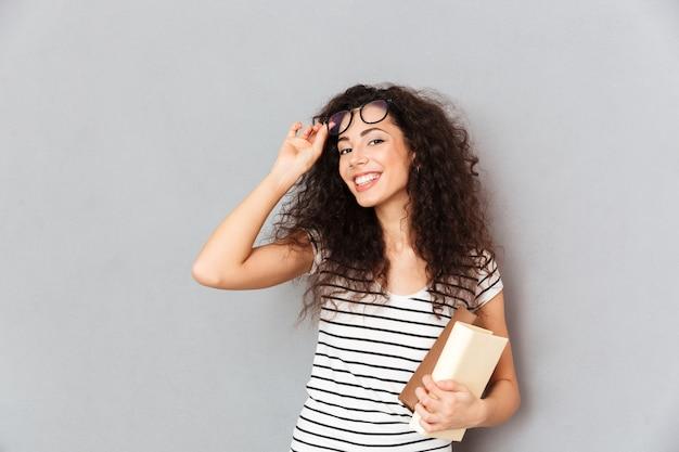 Joven maestra en anteojos con cabello rizado de pie con libros en mano sobre pared gris disfrutando de su trabajo en la universidad siendo inteligente e intelectual