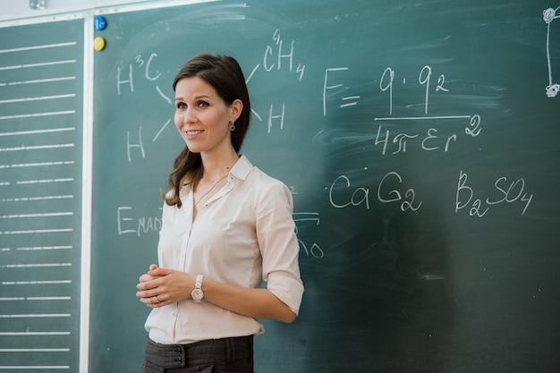 Joven maestra feliz con los brazos cruzados de pie contra el tablero verde