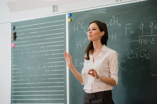 Joven maestra feliz hablando con clase de pie contra el tablero verde