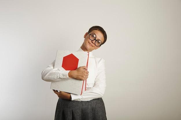 Joven maestra en ropa pasada de moda sosteniendo carpetas rojas y blancas y mirando expectante en blanco