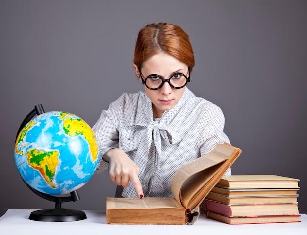 La joven maestra en vasos con libros y globo.
