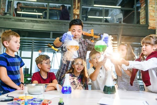 Joven maestro asiático con un grupo de seis alegres alumnos caucásicos de 8-10 años con gafas protectoras durante un experimento químico con líquidos coloreados en la escuela moderna.