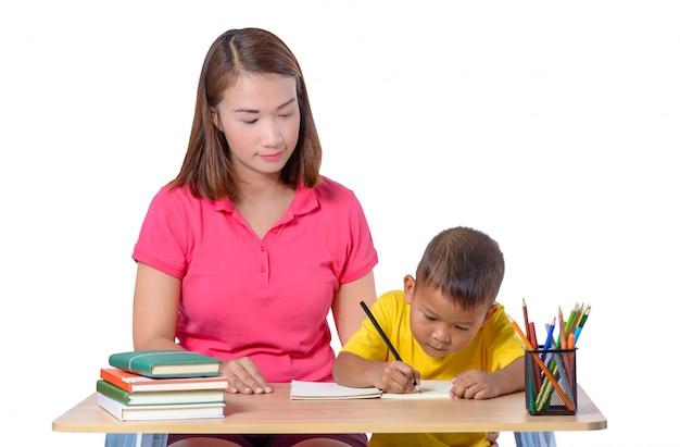 Joven maestro ayudando al niño con la lección de escritura aislado sobre fondo blanco.