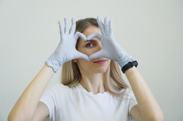 Joven maestro de depilación láser, láser aparte, mujer sonríe, ella está en guantes