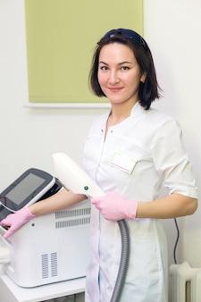 Joven maestro de depilación láser, láser aparte, mujer sonríe. sección de cosmetología depilación