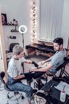 Joven maestro expresivo. atractiva maestra del tatuaje que trabaja con un cliente de cabello oscuro mientras señala el área de tatuajes en el futuro
