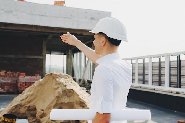 Joven maestro mostrando dónde hacer cambios de edificio en construcción.
