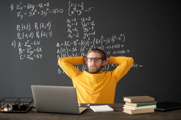 Joven maestro o estudiante en ropa casual mirando la pantalla de la computadora portátil durante la lección de álgebra en línea mientras mantiene sus manos en la parte posterior de la cabeza