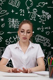 Joven maestro está sentado cerca de la pizarra en el aula