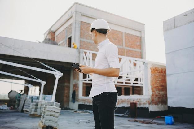 Joven maestro con una tableta en sus manos mirando el edificio en construcción.