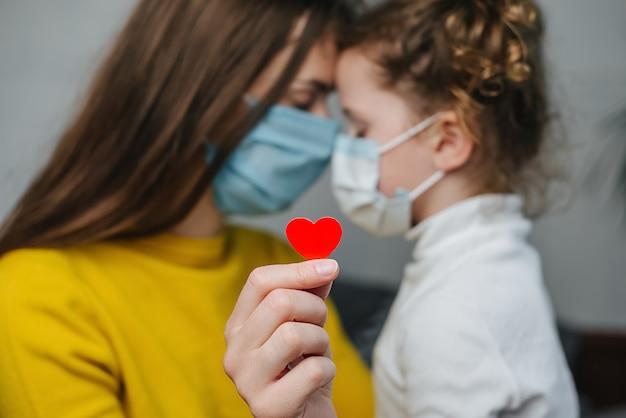 La joven mamá abraza a la linda hija de preescolar con máscaras médicas protectoras sentado en la cama, sosteniendo el corazón rojo como una forma de mostrar agradecimiento y agradecer a todos los empleados esenciales durante las pandemias de covid-19