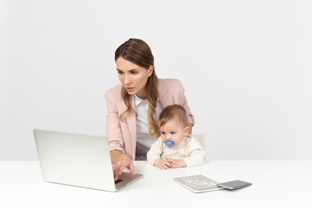 Joven mamá trabajando en computadora y cuidando niños