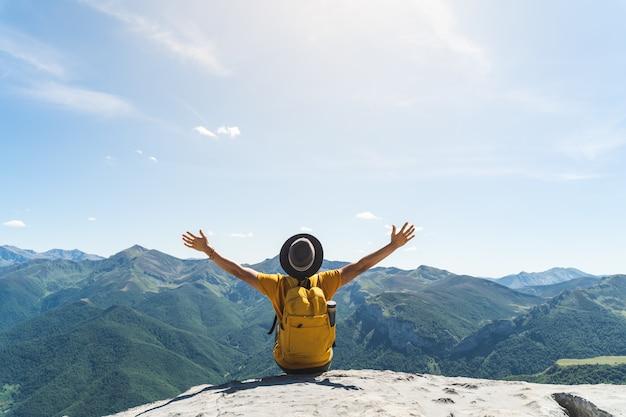 Joven manos arriba sentado en la cima de una montaña.