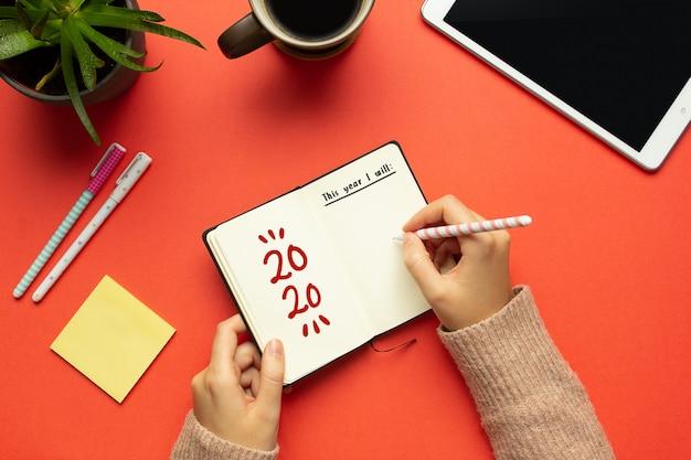 Una joven manos escribiendo en un cuaderno de año nuevo 2020 con una lista de objetivos y objetos sobre fondo rojo.