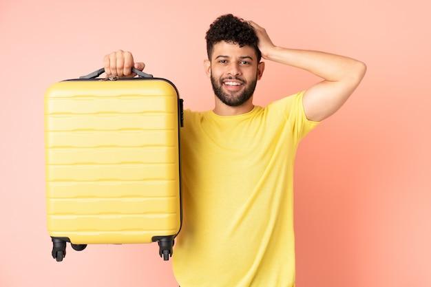 Joven marroquí aislado en la pared rosa en vacaciones con maleta de viaje y sorprendido