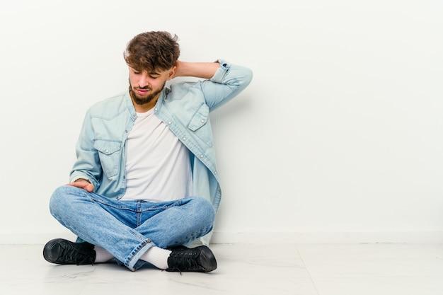 Joven marroquí sentado en el suelo aislado en blanco con dolor de cuello debido al estrés, masajeándolo y tocándolo con la mano.