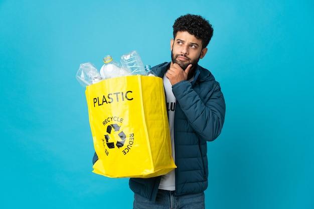 Joven marroquí sosteniendo una bolsa llena de botellas de plástico para reciclar aislado