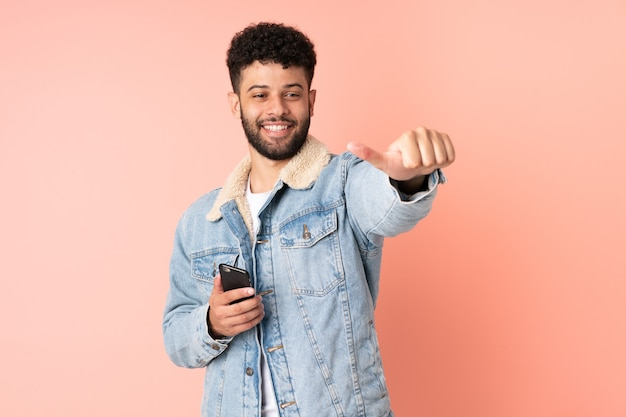 Joven marroquí con teléfono móvil aislado en la pared rosa dando un gesto de pulgar hacia arriba