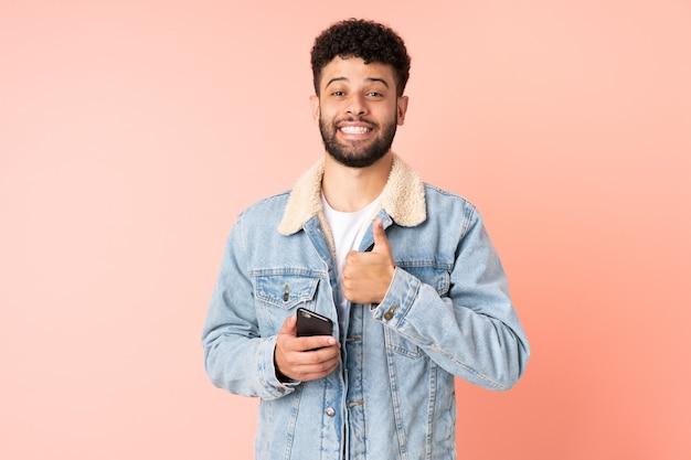 Joven marroquí mediante teléfono móvil aislado sobre fondo rosa dando un gesto de pulgar hacia arriba