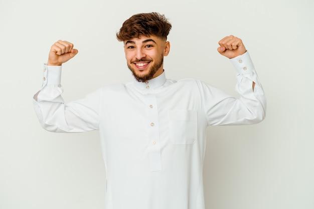 Joven marroquí vistiendo una ropa típica árabe mostrando gesto de fuerza con los brazos, símbolo del poder femenino