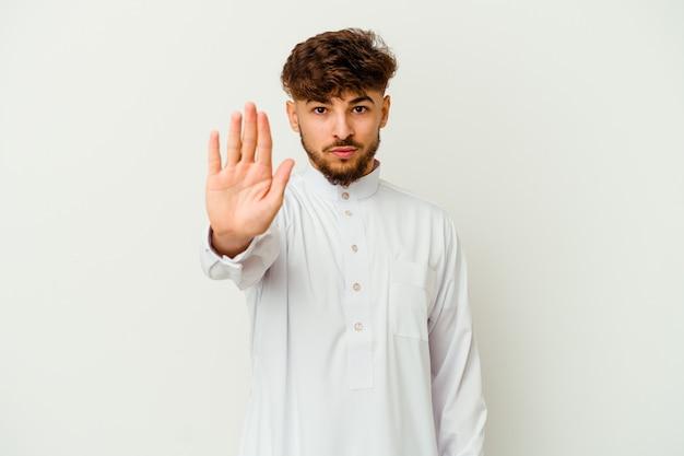 Joven marroquí vistiendo una ropa típica árabe de pie con la mano extendida mostrando la señal de stop, impidiéndote.