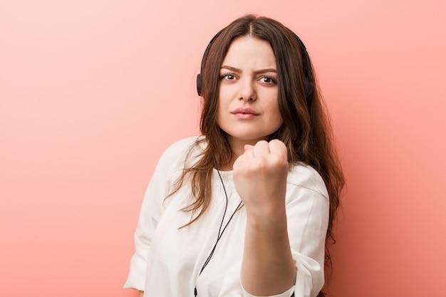 Joven más tamaño mujer con curvas escuchando música con auriculares mostrando puño, expresión facial agresiva.