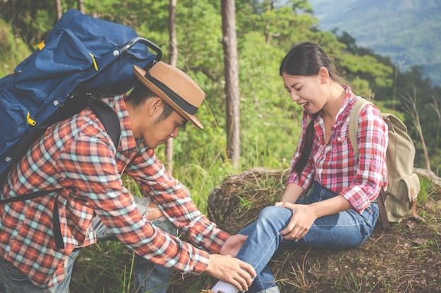 Un joven masajeando las piernas de su novia, que dolor en la cima de la colina en un bosque tropical, aventura de trekking.