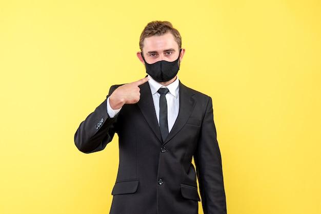 Un joven con una máscara facial que muestra y explica que es obligatorio usar máscara para prevenir la infección por coronavirus en amarillo.
