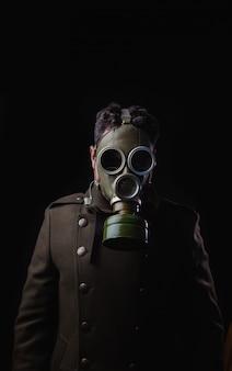 Joven con máscara de gas y abrigo militar