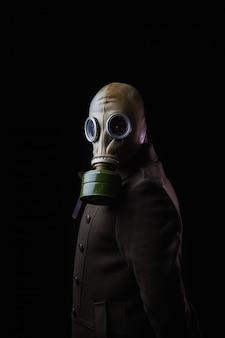 Joven con máscara de gas y abrigo viejo sobre fondo negro