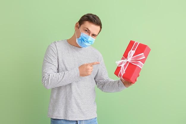 Joven en máscara médica y con regalo en color