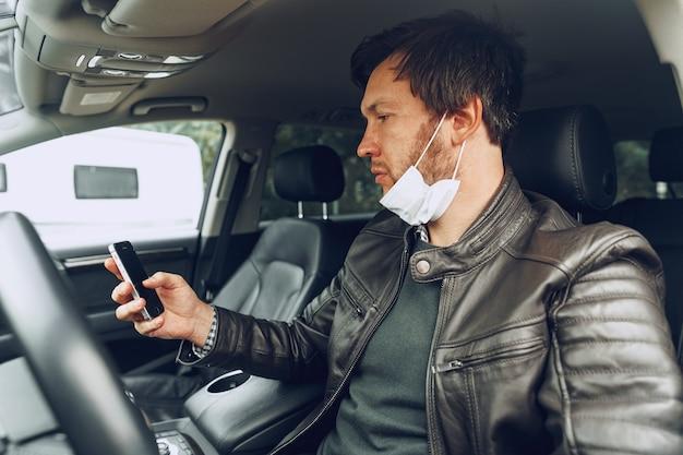 Joven en máscara médica con smartphone en coche