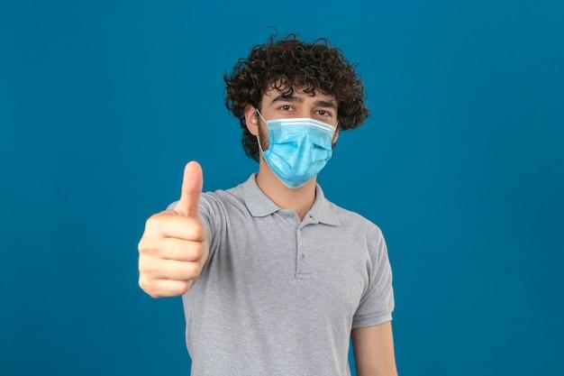 Joven en máscara protectora médica mirando a la cámara con cara feliz mostrando el pulgar hacia arriba sobre fondo azul aislado