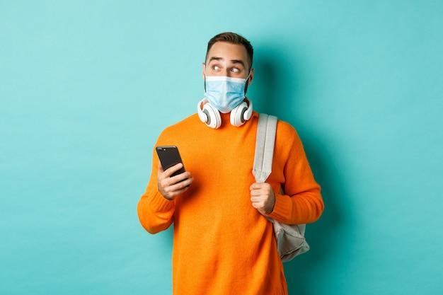 Joven en mascarilla mediante teléfono móvil, sosteniendo la mochila, mirando a la izquierda asombrado