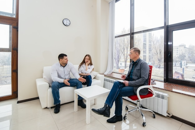 Un joven matrimonio de hombres y mujeres habla con un psicólogo en una sesión de terapia. psicología.