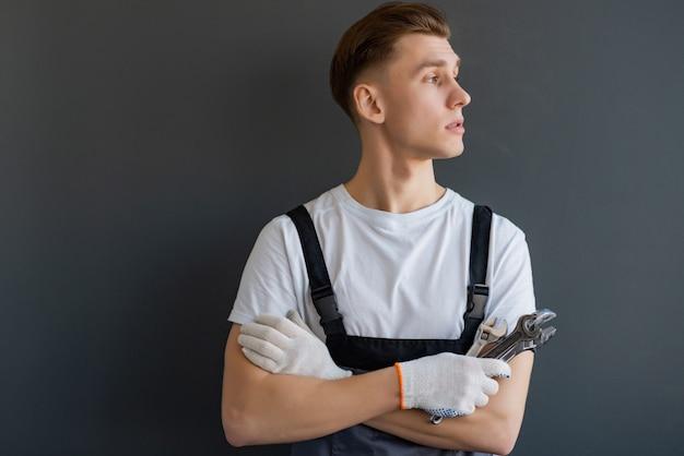 Joven mecánico con brazos cruzados y llave de pie sobre fondo gris