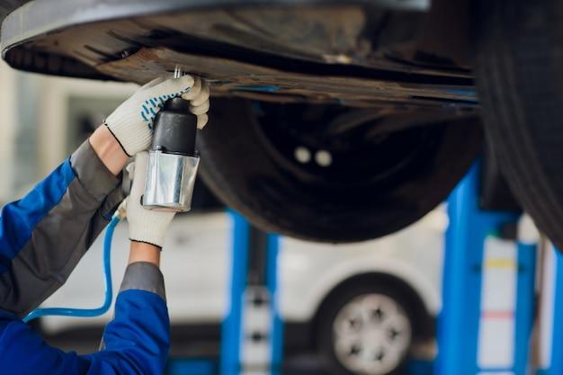 Joven mecánico que fija la rueda debajo del automóvil en servicio